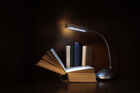 Books and lighting reading lamp on dark background