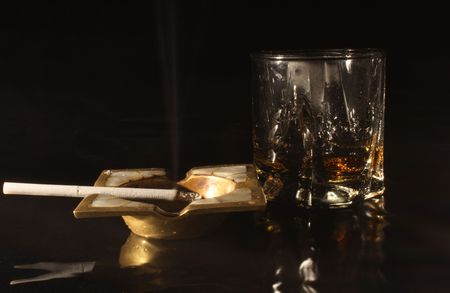 bronzy: Old bronze ash-tray with cigarette and glass of whisky on dark background Stock Photo
