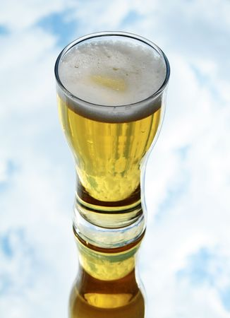 reverberation: Glass of fresh lager beer with reverberation on background with sky and clouds