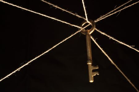 conundrum: Yellow brass key hanging on ropes on dark background