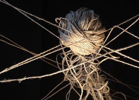 conundrum: Clew e tangled corde appese a sfondo scuro