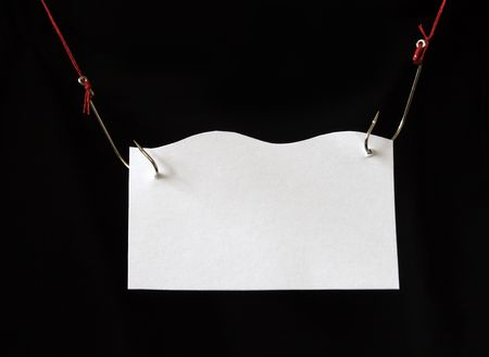nameboard: White papery nameboard hanging with fish-hooks on dark background Stock Photo