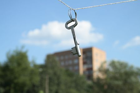 keys to heaven: Key hanging with rope on background with blue sky and building Stock Photo