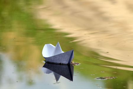 reverberation: White paper boat sailing on background with autumn water