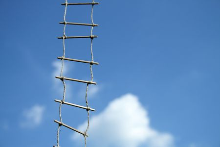 salvaging: Rope ladder hanging on background with blue sky and clouds
