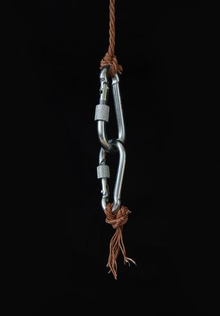 solidity: Two fastened clasps hanging with rope on black background