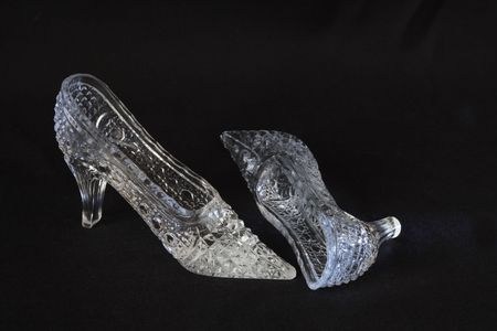 Two nice glass slippers lying on dark background photo