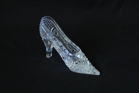 Nice glass slipper standing on dark background photo