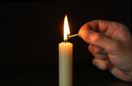 candle wick: Hand with lighting match and candle standing on dark background