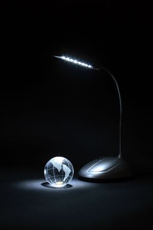 parallel world: Little glassy globe and luminose table lamp on dark background Stock Photo