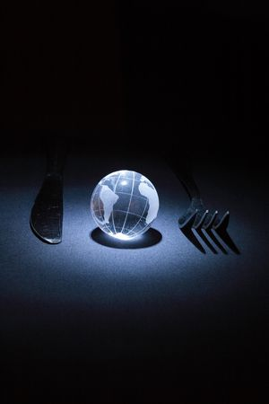 parallel world: Little glassy earth with fork and knife on dark background Stock Photo