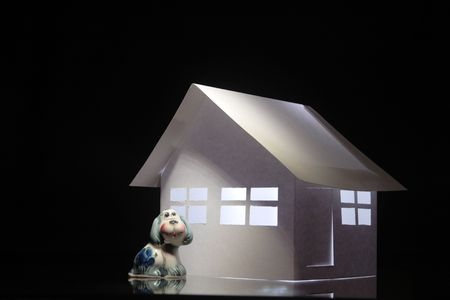 papery: Little toy dog sitting near white papery house on dark background Stock Photo