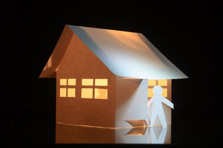 papery: Papery man standing near toy house with luminous windows