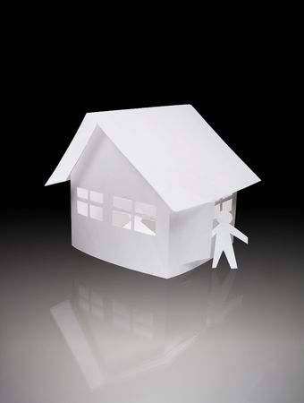 papery: Papery man standing near toy house on glassy background