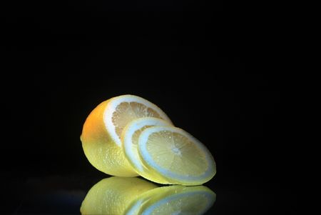 reverberation: Fresh slit lemon with reverberation lying on dark glassy background