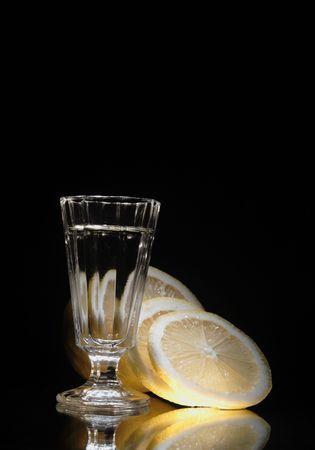 reverberation: Nice little glass of vodka on dark background with yellow lemon