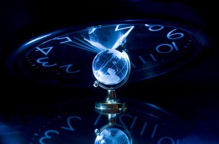 Litte glassy globe on dark background with watch photo