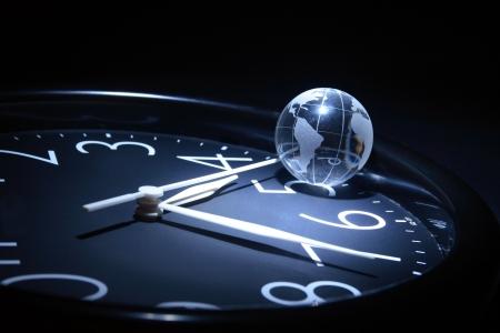 hour hand: Litte glassy globe on dark background with watch