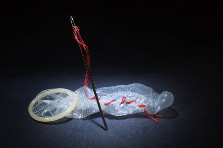 Needle and condom darned with red thread on dark background