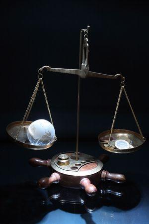 Antique balance with glassy globe and money on dark background Stock Photo - 4139748