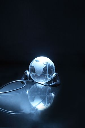 parallel world: Glassy globe with headphones on dark background