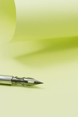 papery: Ancient fountain pen on background with yellow blank papery sheet Stock Photo