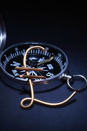 gb pound: Pound sterling sign made from wire lying on dark background with compass