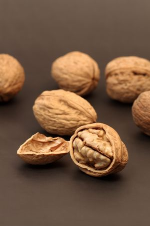 nutshell: Cracked walnut with nutshell on background with walnuts