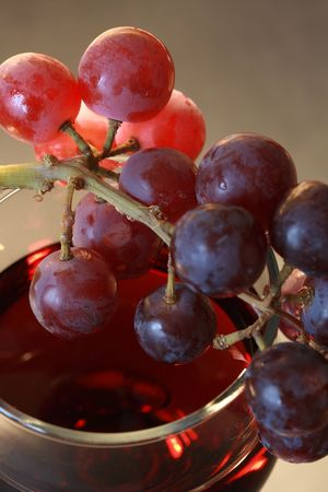 Close-up of bunch of grapes lying on goblet with red wine photo