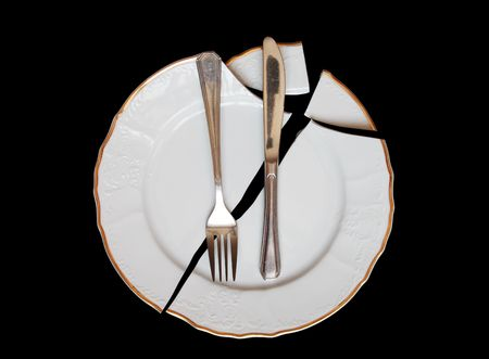 brawl: Forks and knife lying on broken plate isolated on black background Stock Photo