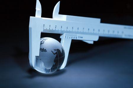 parallel world: Glassy globe inside vernier callipers on dark background Stock Photo