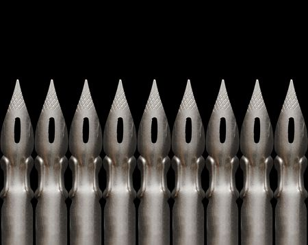 noteboard: Close-up of few old steel pens isolated on dark background Stock Photo