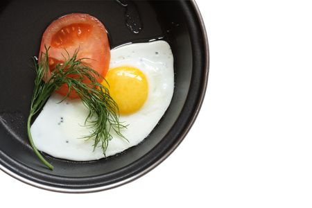 Frying pan with fried egg tomato parsley isolated on white photo