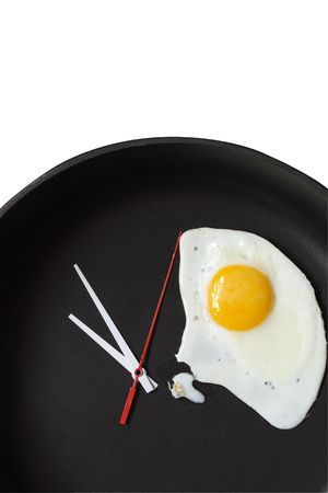 Clock hands and fried egg lying on black frying pan Stock Photo - 4561172