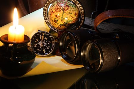 Still-life with vintage compass binoculars globe on dark background