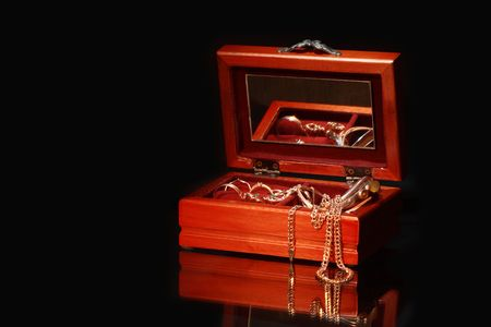 Nice wooden casket with jewelry on dark background