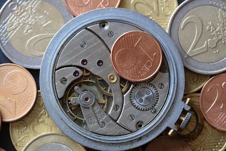 Opened watch mechanism lying on european coins background photo