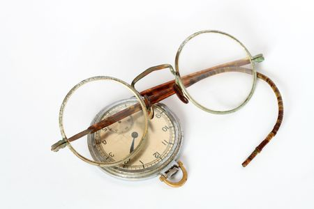 exactness: Vintage spectacles and watch lying on white background