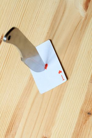 throwing knife: Direct hit to playing card with missile knife on wooden background Stock Photo