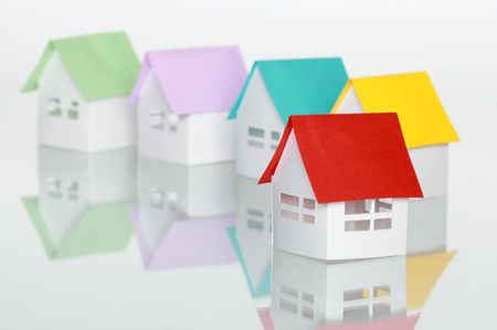 papery: Few toy papery houses with colored roofs standing on white background Stock Photo