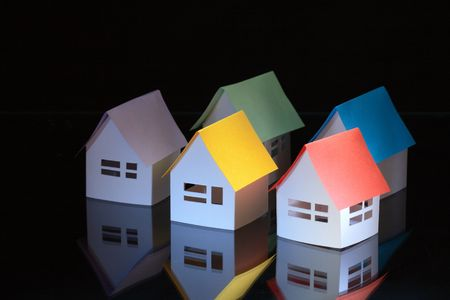 papery: Few toy papery houses with colored roofs on dark background Stock Photo
