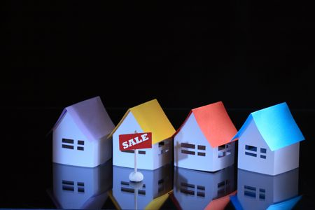 papery: Few papery houses with colored roofs and sale tablet on dark background