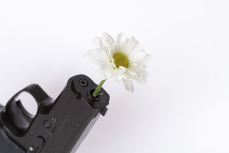 backsight: Black modern automatic pistol with flower isolated on white background