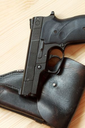 backsight: Modern automatic pistol and old leather holster on wooden background