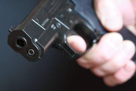 pr�voyance: Close-up de l'homme avec un pistolet automatique sur fond sombre