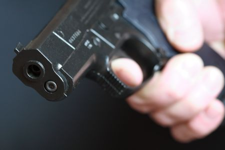 backsight: Close-up of man hand with automatic pistol on dark background