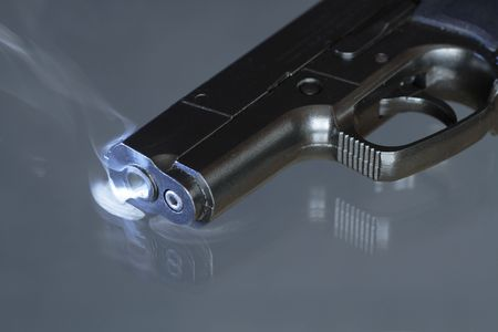 backsight: Black automatic pistol with smoke near barrels hole lying on dark background