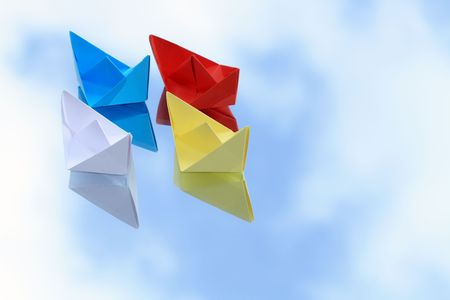 Colorful paper boats isolated on background with blue sky photo