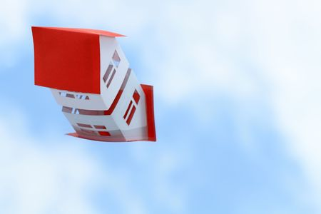 White paper house with red roof on blue sky background  photo