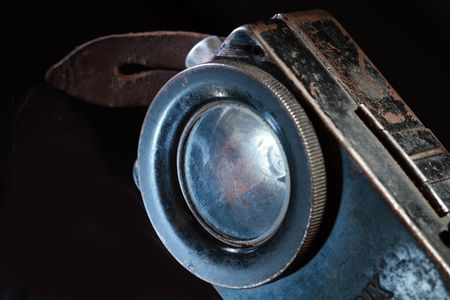 torchlight: Close-up of old rusty pocket flashlight on dark background